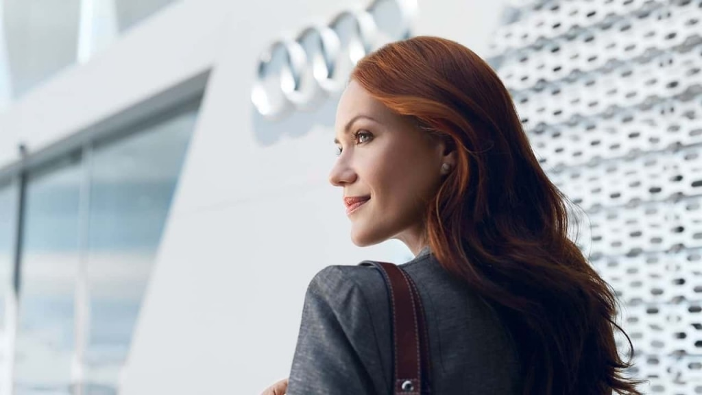 About us - Business woman in front of Audi building